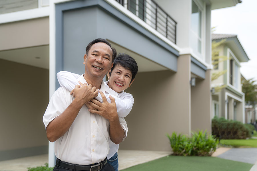 Insurance Quote - Smiling Mature Couple Standing Outside Their Home