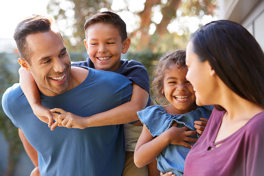 Personal Insurance - Happy Family with Two Kids Playing Outside