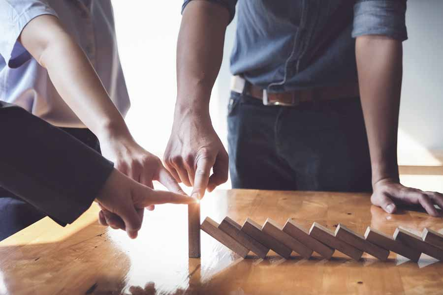 Programs - Three Business Professionals Collaborating to stop Dominoes from Falling